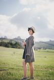 Beautiful young woman in a jeans dress and straw hat posing on a green meadow Royalty Free Stock Photos