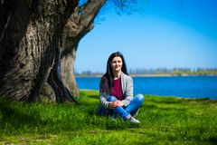 Beautiful young woman in jeans sits on river bank near big tree royalty free stock photos