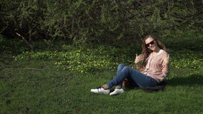 Beautiful young woman in jeans sitting happily in lush green grass in a summer park under sunlit trees stock footage