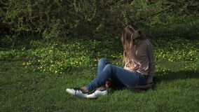Beautiful young woman in jeans sitting happily in lush green grass in a summer park under sunlit trees stock video