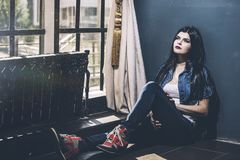 Beautiful young woman in jeans and sneakers in front of large Wi royalty free stock images