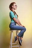 Beautiful young woman in jeans and sneakers. Happy girl in sunglasses. beautiful young woman in jeans and sneakers smiles and sits on a chair Royalty Free Stock Photo