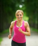 Beautiful young woman jogging in the park Royalty Free Stock Photos