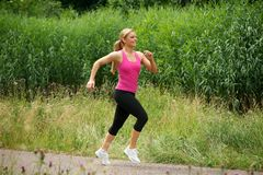 Beautiful young woman jogging in the park Royalty Free Stock Photo