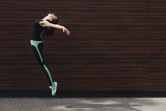 Beautiful young woman jumping against brick wall Stock Image