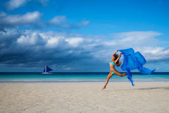 Beautiful young woman jumping on the beach with a blue tissue. The sea in the background royalty free stock photos