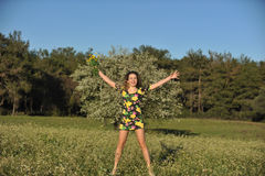 Beautiful young woman jumping in blooming meadow Stock Image