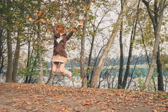 Beautiful young woman jumping in a city park Stock Photos