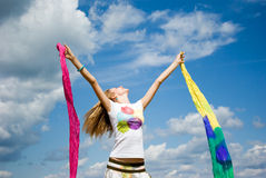 Beautiful young woman jumping on field in summer Stock Photos