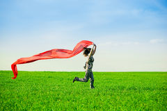 Beautiful young woman jumping on a green meadow Royalty Free Stock Photos