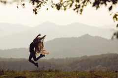 Beautiful young woman jumping on a green meadow with a colored tissue. Stock Photos