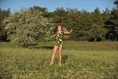Beautiful Young Woman Jumping In Blooming Meadow Stock Photo