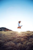 Beautiful young woman jumping on a meadow in the mountain Stock Photos