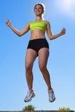 Beautiful young woman jumping outdoors Stock Photos