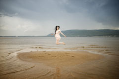 Beautiful young woman jumping on a sandy beach Royalty Free Stock Images