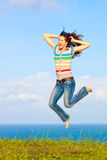 Beautiful young woman jumping up in the air Stock Photography