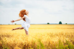 Beautiful young woman jumping at wheat field Stock Photo