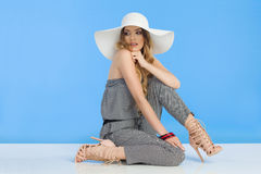 Beautiful Young Woman In Jumpsuit And White Sun Hat Is Sitting And Looking Away Over Shoulder Royalty Free Stock Images
