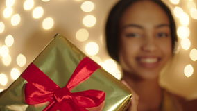 Beautiful young woman keeping big gift box in her hands and smiling stock video