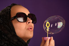 Beautiful young woman in kerchief blowing bubbles Royalty Free Stock Image