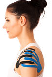 Beautiful young woman with kinesiotape on her shoulder to mobili Stock Images