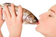 Beautiful young woman kissing a fish Royalty Free Stock Image
