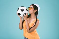 Beautiful young woman kissing a football Royalty Free Stock Images
