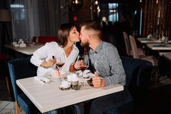 Beautiful young woman kissing her man`s nose in a restaurant royalty free stock images