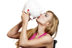 Beautiful young woman kissing piggybank isolated on white Royalty Free Stock Photos