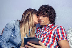 Beautiful young woman kissing to man looking Royalty Free Stock Photography