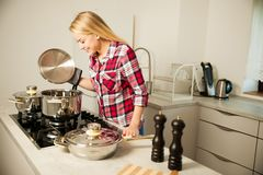 Beautiful young woman in kitchen cooks a delicious meal.  royalty free stock image