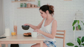 Beautiful young woman in kitchen dancing in the morning. Brunette girl wearing pajamas haves breakfast at home. Happy morning in light apartment, enjoying the Royalty Free Stock Images