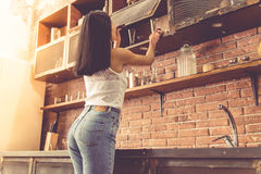 Beautiful young woman in kitchen Stock Photos