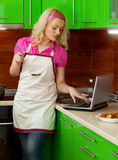 Beautiful young woman in the kitchen using a laptop Royalty Free Stock Photography