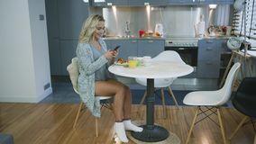 Attractive woman using smartphone during breakfast. Beautiful young woman in knitted jacket sitting at kitchen table and browsing smarthone during nice breakfast stock video