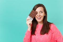 Beautiful young woman in knitted pink sweater looking aside hold in hand covering eye with chocolate bar isolated on. Blue wall background studio portrait royalty free stock images