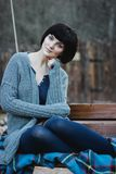 Beautiful young woman in knitwear sitting on a swing Stock Photography