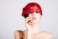 Beautiful Young Woman with a Lace Headpiece. A glamorous, high fashion woman looks at the camera while posing with red lace headpiece on her head and bare Stock Photo