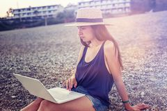 Beautiful young woman with a laptop on the beach at sunset. Beautiful young woman with a laptop on the beach at bright sunset Stock Photos