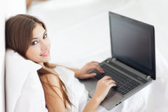 Beautiful young woman with laptop on bed Stock Photography