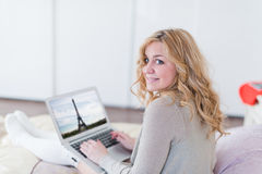 Beautiful young woman with laptop on bed Royalty Free Stock Image
