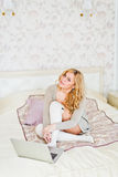 Beautiful young woman with laptop on bed Stock Photo
