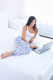 Beautiful young woman with laptop in bed Royalty Free Stock Photography