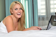 Beautiful young woman with laptop in bed Stock Images