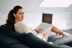 Beautiful young woman with a laptop on couch Royalty Free Stock Photography