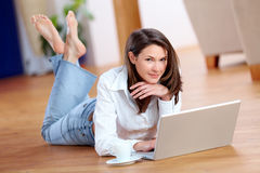 Beautiful young woman with laptop on the floor Stock Photos