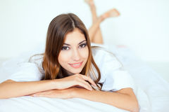 Beautiful young woman in large shirt on bed Royalty Free Stock Photos