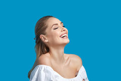 Beautiful young woman laughing on blue background. Royalty Free Stock Image