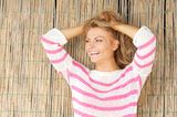 Beautiful young woman laughing with hands in hair Stock Images
