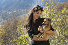 Beautiful young woman laughing and  hugging dog. Happy girl  hugging dog outdoor Royalty Free Stock Photo
